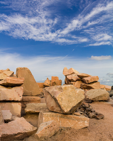 rock pile: Large rock pile brown, which is located on the sand under a cloud sky beautiful. Stock Photo