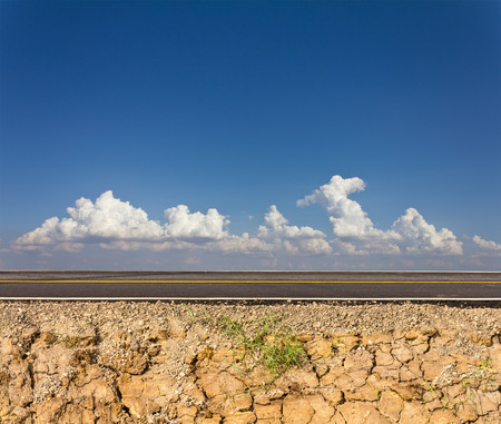 Side road in the countryside with cracked soil below and cloudy sky in the background.