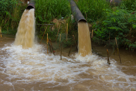 Water flow blur emanate from the sewer into the river which is grasscovered coast. photo