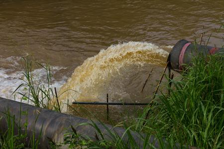 Grasscovered 海岸である川に下水から水の流れを停止します。