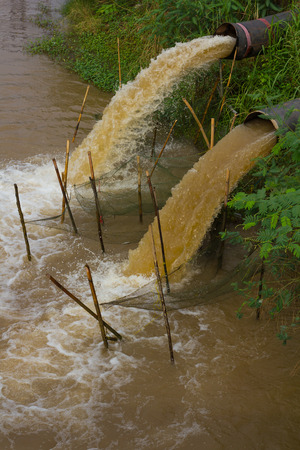 polluting: Water flow stops away from the sewer into the river which is grasscovered coast. Stock Photo