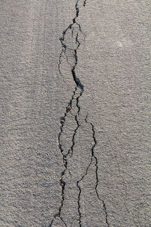 road surface: Close up asphalt road surface crack as long as fragile and heavy trucks passing by. Stock Photo