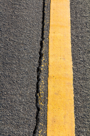road surface: Close up cracked asphalt surface of the road with a yellow line Thailand.