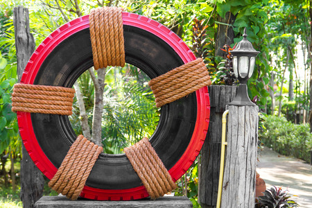 Tires Wheels black with a red tie with a brown manila rope is decorated in a beautiful garden.