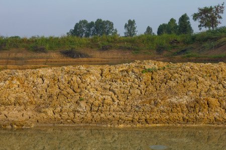 coastal erosion: Background soil surface water flows through coastal erosion for a long time seen as a layer. Stock Photo