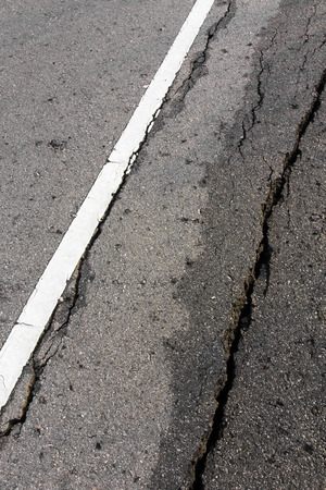 rough road: Cracks near the white line on the road surface is rough and wet from the rain. Stock Photo