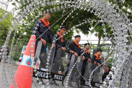 razorwire: BANGKOK THAILANDAUG 8:Peep through the barbed wire to a police riot shield of Thailand which breaks in a row.On August 8 2013 in Bangkok Thailand. Editorial