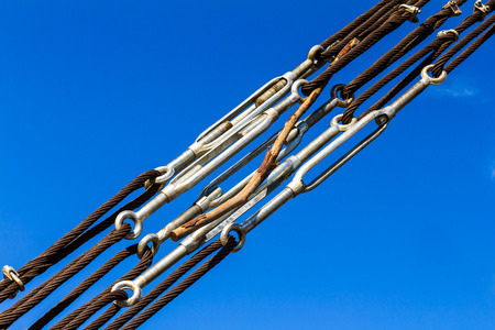 slings: Close up of wire rope stretched taut with strong joints with wood stuck through the sky.