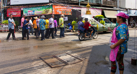 a white police motorcycle: Thailand women use a hose to spray water to people walking on the street in festival.On July 9, 2013 in Phichit, Thailand. Editorial