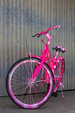 medium size: Medium size mountain bike with pink spray the body beautifully located near the walls of zinc.