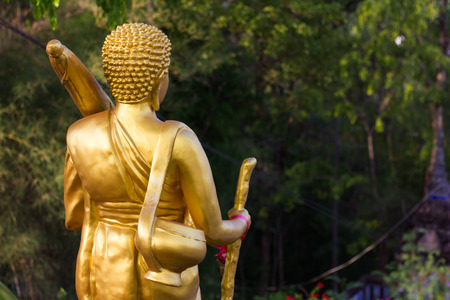 limosna: Behind the statue golden Buddhist monk who went on a pilgrimage for alms in the countryside.