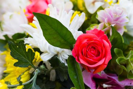 Roze rozen met witte bloemen en gele versieringen prachtig samen, maar verwelken.