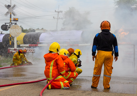 fireman with hose: Team Thailand firefighters extinguished the blaze, flames, smoke close to the train tanker, which is dangerous.
