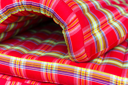 upholster: Close-up mattress, which curled red cloth twisted into a half circle indicates the strength soft. Stock Photo