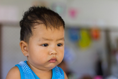 sullen: Close-face sullen frown upset child in Thailand, where facial expressions and eyes innocent.