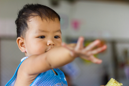 Children reach out to the development in infancy while eating boiled corn.