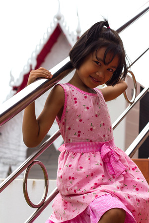Girl wearing a pink shirt, smiling shyly by bonding stainless steel railings on the stairs in a temple of Thailand. photo