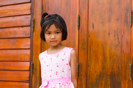 A girl wearing a pink shirt standing smiling concern naive closely with wooden doors in the ancient temple. photo