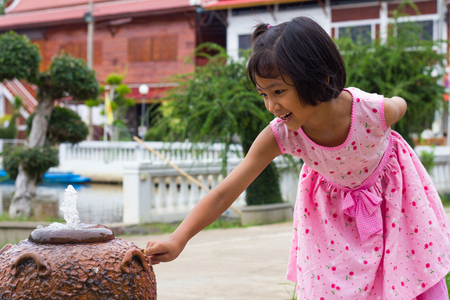 Thailand girl wearing pink are leaning dip a finger on the jar fountain in a Buddhist temple. photo