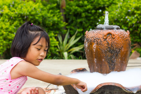 Thailand girl wearing pink shirts are dipped his finger in the pot bubble play into the jar fountain. photo