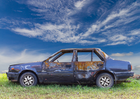 Blue saloon car which caught fire devastated the park on the grass with the sky as a backdrop.