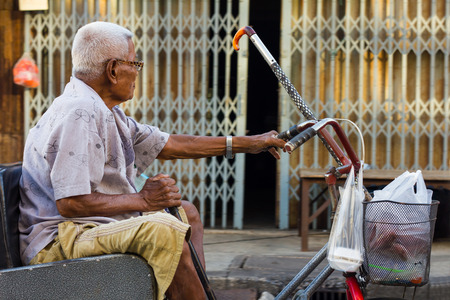 adapted: PHICHIT THAILAND-JUNE 19: Thailand elderly man whose wheelchair adapted bike lever handle and a steel door into the house..On June 19, 2015 in  Phichit, Thailand. Editorial