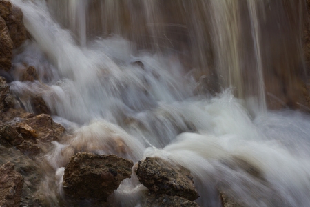 tides: Close up of waterfall flowing over rocks and tides blurred and eroded clay frantically. Stock Photo