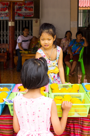 traded: PHICHIT THAILAND-AUGUST 8:Both girls are playing traded goods or  candy and have fun with people sitting watched.On August 8, 2015  in Phichit, Thailand.