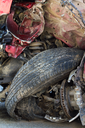 accident body: Close down the front of the red car is wrecked in an accident collision crumpled steel wheel tire burst. Stock Photo