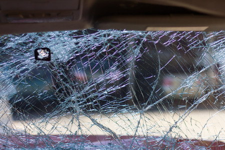 Looking from the inside through the broken windshield of a car accident, which was parked in front. Stock Photo