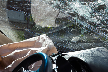 Inside the car, sunny, with airbags and windshield cracks due to accident damage. Archivio Fotografico