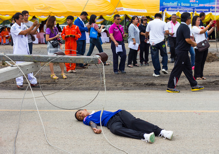 cross street with care: PHIcHIT THAILAND-AUGUST 7: People shooting drills, training accidents, which are the boys lying dead on the road over a power pole.On August 7, 2015 in Phichit, Thailand. Editorial