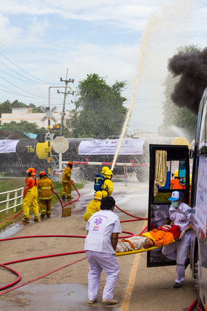 PHICHIT THAILAND-AUGUST 7:Firefighters were spraying water on the train, truck and rescue stretcher bearers people off the bus.On August 7, 2015 in Phichit, Thailand.