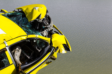 scrap car: View from the top front of the yellow car, which was demolished in the accident, floating on the water.