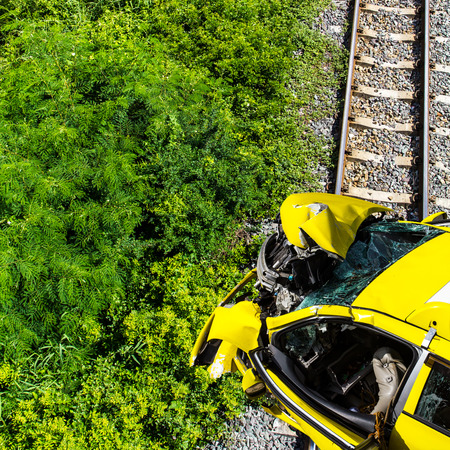 Top view of yellow car, which was devastated by the accident, which is blocking the railroad.