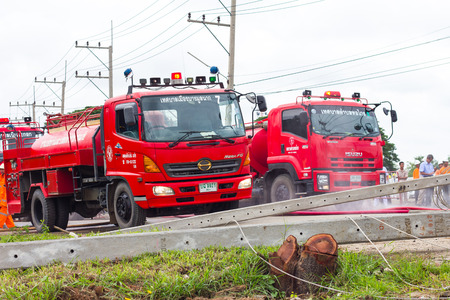 guarded: PHICHIT THAILAND-AUGUST 7:Fire engine red, both were guarded parking on the road with power poles toppled barricades.On August 7, 2015 in Phichit, Thailand.