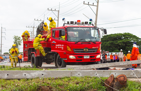 barricades: PHICHIT THAILAND-AUGUST 7:Officer or firefighter was climbing down  from a fire engine red, with power poles toppled barricades  road.On August 7, 2015 in Phichit, Thailand.