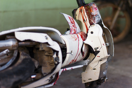 Close up the front mudguard white blur motorcycle with blood and broken headlights of an accident.