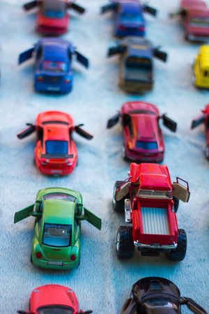 bigfoot: View from the top of toy cars, which lay in a row on white lined focus on Bigfoot red car. Stock Photo