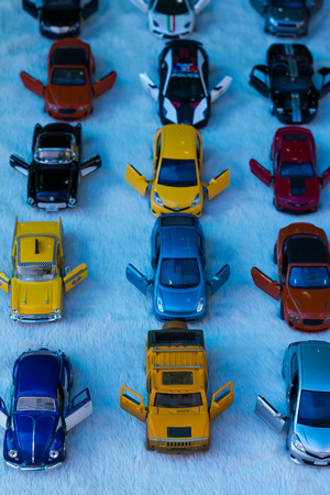 bourne: View from above of toy soldiers, who placed a row of yellow mixed in with the coupe variants. Stock Photo