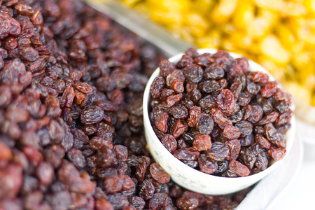 palatable: Dried fruits, raisins, which are stacked together separated in cup white palatable.