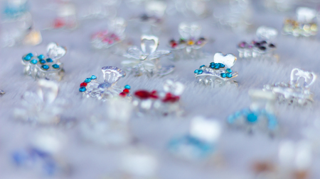 fake diamond: Close fake diamond Rings in stainless steel blue blur plug placed in rows on a white cloth. Stock Photo