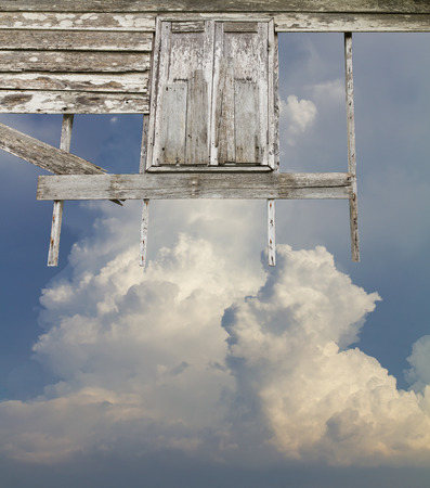 wafting: Background wall old wooden window decay wafting on the air, with the sky and clouds as a backdrop.
