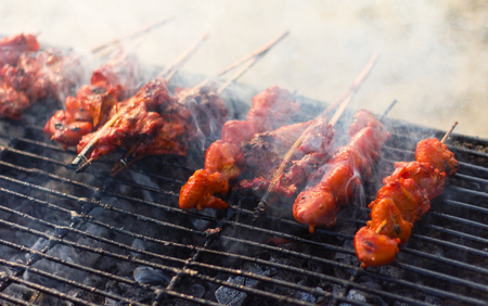 scorched: Grilled chicken skewers on grill on charcoal smoked steel fire scorched nearly as appetizing. Stock Photo