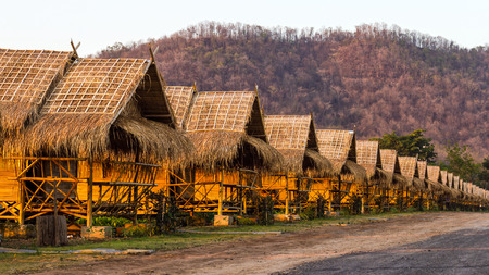 small house: Straw, bamboo, thatch-roof cottage resort on the grass on a dirt road lined with mountains as a backdrop. Stock Photo