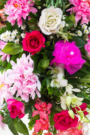 fabrication: Background of roses and fake flowers, plastic fabrication, which placed a bouquet of blooming beautifully. Stock Photo