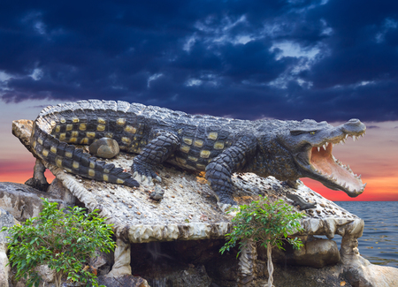 agape: Statue large crocodile was agape, which is located on a rocky river and Cloudy backdrop. Stock Photo