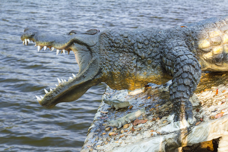 agape: Close agape crocodile statue on a rock with the waves blur the background.