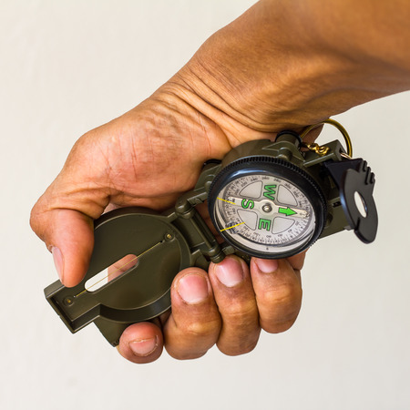 clutching: Close-skinned man with red hands were clutching a compass to find the direction of a white wall as a backdrop.