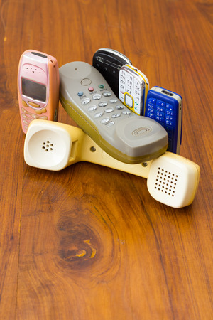 ancient telephone: Telephone and mobile versions of old traditional and placed the overlap onto a wooden ancient pattern. Stock Photo
